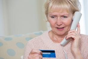 An elderly woman giving her credit card information to a scammer on the phone